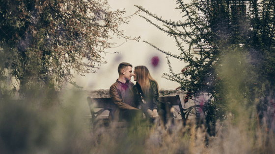 a couple sitting in a bench at the park